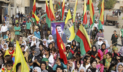 Syrian Kurds demonstrators hold portraits of jailed Kurdistan Workers Party leader Ocalan during a protest in Derik