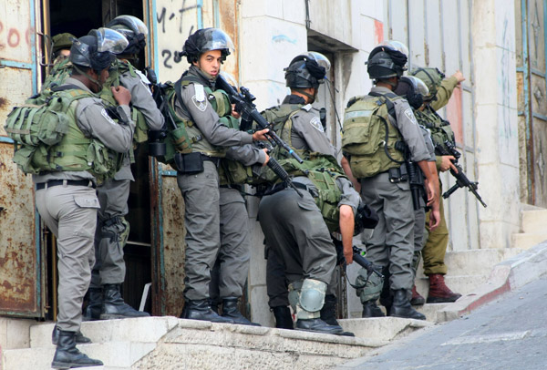 Israeli soldiers gather before starting a patrol in the West Bank city of Hebron