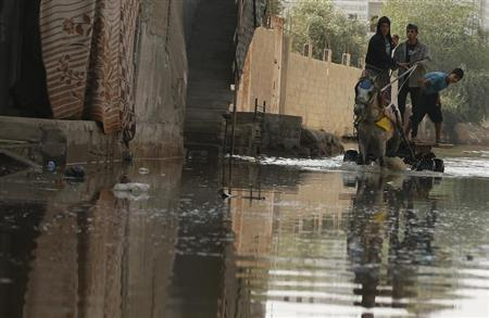 Palestinians ride a horse cart on a street flooded with sewage water from a sewage treatment facility in Gaza City