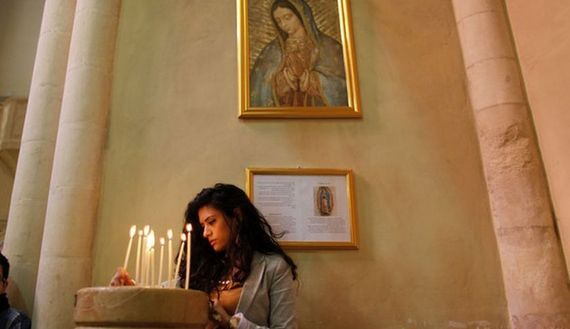 A Palestinian Christian lights a candle during a prayer to show solidarity with Gaza, at a Catholic church in the West Bank town of Beit Jala near Bethlehem