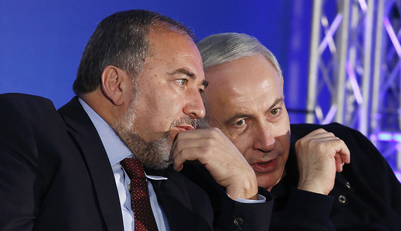 Israel's Prime Minister Netanyahu converses with former Foreign Minister Lieberman during a campaign rally in Ashdod