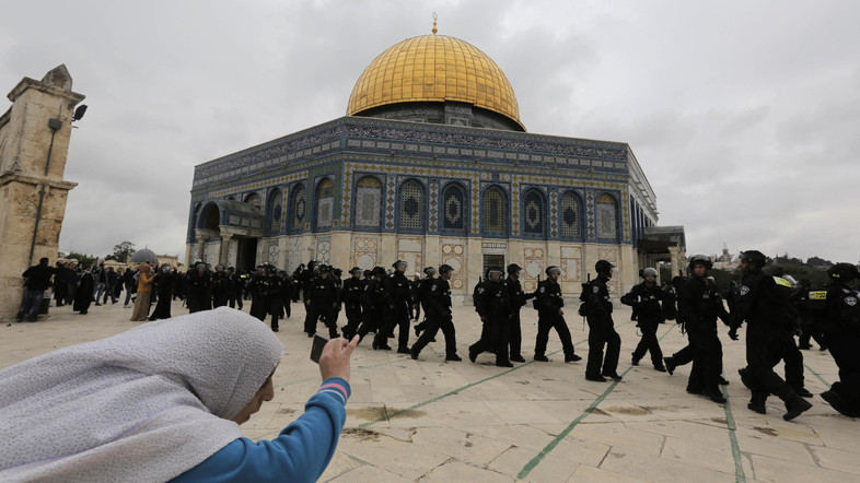 A Palestinian woman takes a picture as Israeli police walk in front of the Dome of the Rock during clashes with stone-throwing protesters in Jerusalem's Old City