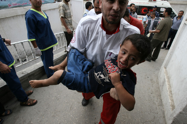 A member of the Palestinian Red Crescent Society carries an injured child at an hospital in Rafah