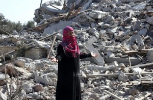 A Palestinian woman gestures as she walks past a houses damaged by what police said were Israeli air strikes and shelling in Khuzaa, east of Khan Younis