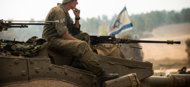 "KAFAR AZZA, ISRAEL - JULY 28: An Israeli soldier sits on a tank on July 28, 2014 near Kafar Azza, Israel. As Israel's operation ""Protective Edge"" in Gaza continues, the international community struggles to find a truce agreement. (Photo by Andrew Burton/Getty Images)"