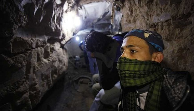 A Palestinian works inside a smuggling tunnel flooded by Egyptian forces, beneath the Egyptian-Gaza border in Rafah, in the southern Gaza Strip February 19, 2013. Egypt will not tolerate a two-way flow of smuggled arms with the Gaza Strip that is destabilising its Sinai peninsula, a senior aide to its Islamist president said, explaining why Egyptian forces flooded sub-border tunnels last week. To match Interview PALESTINIANS-TUNNELS/EGYPT REUTERS/Ibraheem Abu Mustafa (GAZA - Tags: POLITICS CIVIL UNREST) - RTR3DZNQ