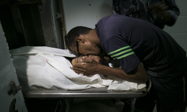A Palestinian man mourns over the body of 16-year-old Abdel Rahman al-Dabbagh, who according to the health ministry was shot dead by Israeli troops during clashes near the border fence, at a hospital morgue in the central Gaza Strip, on September 9, 2016. Ministry spokesman Ashraf al-Qodra identified the teenager as Abdel Rahman al-Dabbagh, and said he was killed east of Bureij refugee camp in central Gaza, saying the teenager was hit in the head and taken to hospital where he was pronounced dead.The Israeli army said that their troops only used tear gas to disperse the youths.  / AFP PHOTO / SAID KHATIB