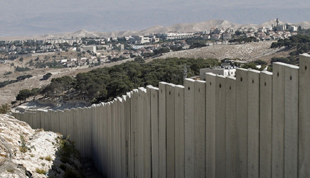 A picture taken on October 21, 2014 in the West Bank village of Zayem near Jerusalem, shows the Israel's controversial separation barrier with the Jewish settlement of Maale Adumim in the background.  AFP PHOTO/AHMAD GHARABLI        (Photo credit should read AHMAD GHARABLI/AFP/Getty Images)