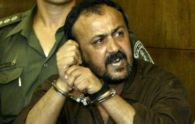 """Marwan Barghouti, 43, (R), general secretary of Palestinian [President Yasser Arafat's Fatah ] movement in the West Bank, speaks to the press as his attourney Jamal Bulous (L) tries to stop him at Tel Aviv's city court on August 14, 2002. Shouting in Hebrew, """"the Intifada will win"""", Marwan Barghouti entered the Israeli court on Wednesday to face murder charges in Israel's first civilian trial of a popular leader of Palestinian uprising. - RTXLG9J"""